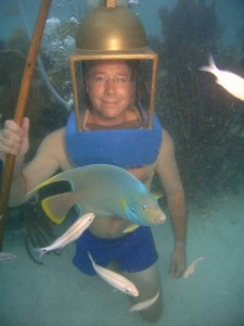 Happy helmet diver with only one leg, using a stick for balance, posing with Diana the Angelfish.