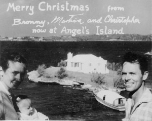 Black and white photo taken in 1955 of Mr. and Mrs. Bronson Hartley, in Bermuda with Harrington sound in the background, with home on angel's island in the center.