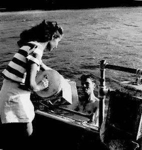 Bronson Hartley's wife lowering his diving helmet into the water in the early days of Bermuda