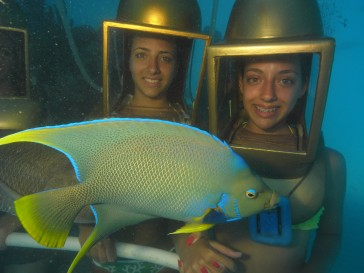 Photo of two female helmet divers, with an angelfish in foreground