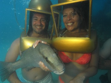 Grey snapper being held by a helmet diving couple.