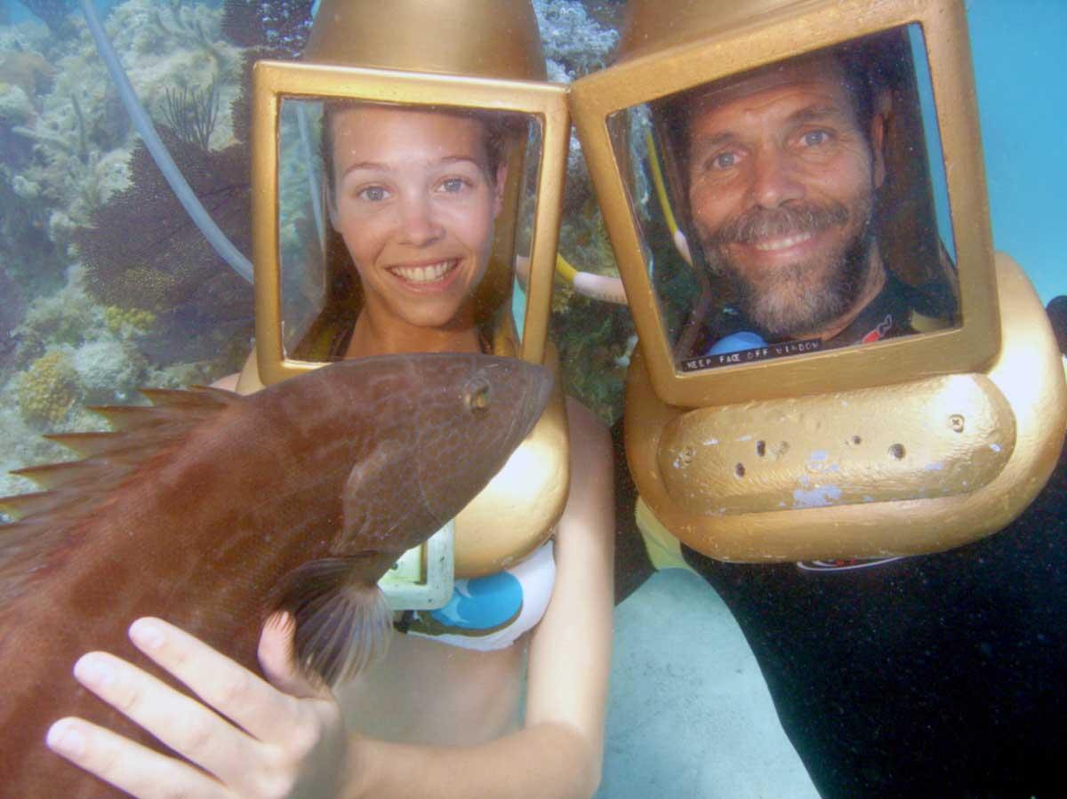 helmet diver holding a grouper